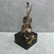Zilveren viool op marmeren sokkel