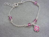 Zilveren Kinder armbandje met bloem en roze kraaltjes.